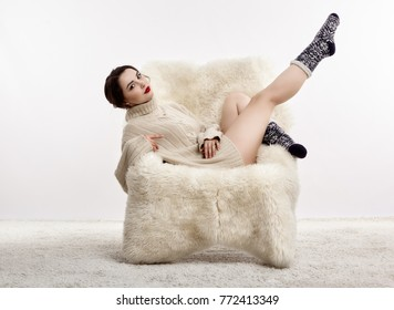 Portrait of beautiful brunette woman with leh up. Female is dressed in white cashmere sweater and woolen socks. Girl is sitting on white fur arm-chair  staying on furry carpet