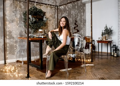 Portrait of beautiful brunette woman in lights in interior of  holiday Christmas. Gorgeous brunette girl sitting on chair. Fashion girl. Happy New Year. Woman in  in decorated house.happy New Year.