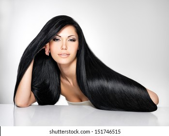 Portrait of a beautiful brunette woman with long straight hair poses at grey background