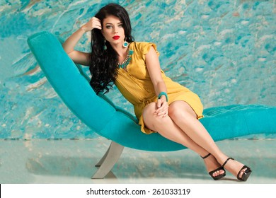Portrait of a beautiful brunette woman with long hair relaxing on modern chair
