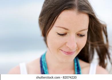 Portrait of a beautiful brunette woman looking down