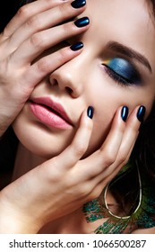 Portrait of beautiful brunette woman on black background. Female with blue eye shadow make up and manicure. Girl with closed eyes and peacock feather earrings