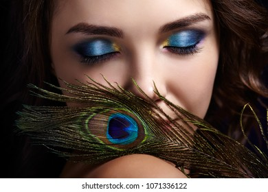 Portrait of beautiful brunette woman on black background. Female with blue eye shadow make up and manicure. Girl with eyes closed and  peacock feather in hand