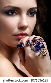 Portrait of beautiful brunette woman on black background. Female with blue eye shadow make up and manicure