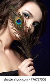 Portrait of beautiful brunette woman on black background. Female with blue eye shadow make up and manicure. Girl with peacock feather