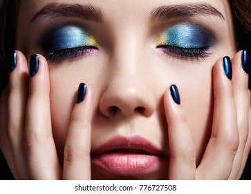 Portrait of beautiful brunette woman on black background. Female with blue closed eyes shadow make up and hands near face with professional manicure