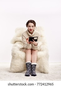 Portrait of beautiful brunette woman with phone in hands. Female is dressed in white cashmere sweater and woolen socks. Girl is sitting on white fur arm-chair  staying on furry carpet