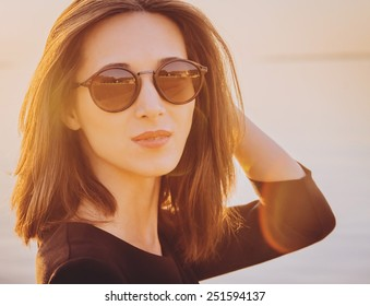 Portrait of beautiful brunette woman in round sunglasses on beach at sunny day. Image with sunlight effect