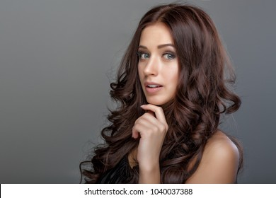 portrait of a beautiful brunette woman with shiny silky long curly hair
