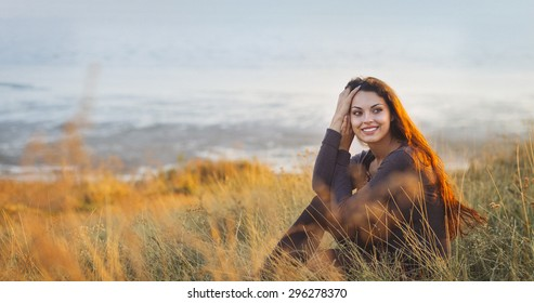 Portrait of the beautiful brunette woman at the windy autumn day relaxing on coast feeling good
