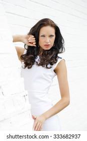 Portrait of beautiful brunette women in white dress leaning on the wall