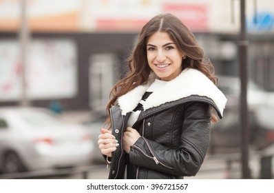 A portrait of a beautiful brunette young Caucasian woman outdoor. Young smiling woman outdoors portrait. Soft sunny colors.Close portrait.