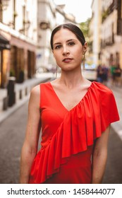 Portrait of beautiful brunette young woman with topknot hairstyle wearing red ruffles dress walking on the street. Fashion photo, looking to the camera.