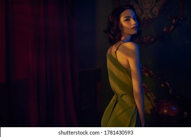 Portrait of a beautiful brunette young woman in a light elegant dress posing in a dark vintage room lit by the rays of the setting sun. Beauty, fashion concept. Evening make-up and hairstyle.