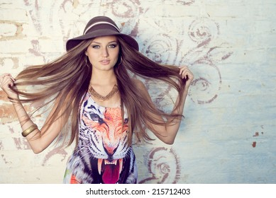 portrait of beautiful brunette young woman with long luxury hair having fun relaxing posing on summer green outdoors copy space background