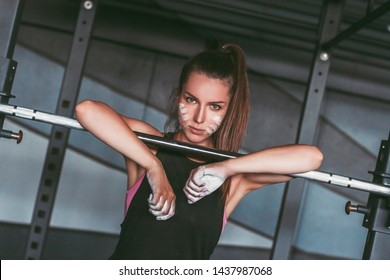 Portrait beautiful brutal athletic woman with workout dust on face and hand leaning on barbell bar in dark gym. Young determined fitness girl posing while exercising with barbell in gym. Weightlifting