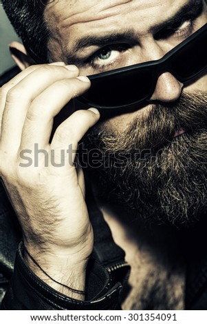 Portrait of beautiful brutal unshaved male biker with long beard and moustache touching black sunglasses with hand looking forward closeup, vertical picture