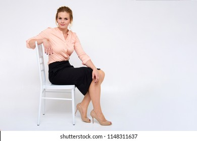 Portrait of a beautiful business blonde girl sitting on a chair on a white background. She is right in front of the camera in different poses