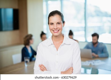 Portrait of beautiful business executive standing with her arms crossed in office