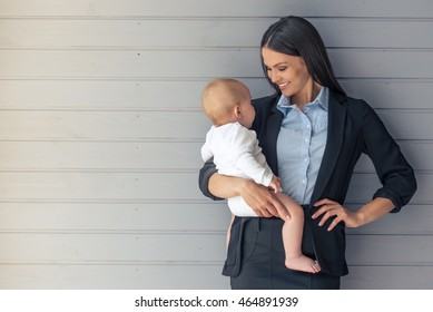 Portrait of beautiful business lady in classic suit and her sweet little baby looking at each other and smiling standing before gray wall