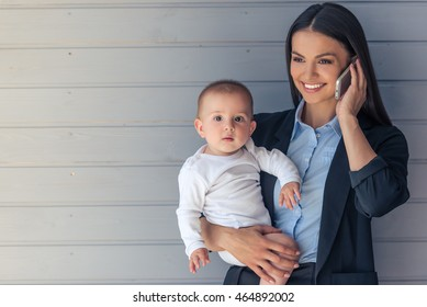 Portrait of beautiful business lady in classic suit and her sweet little baby on gray background. Mom is talking on the mobile phone and smiling, baby is looking at camera