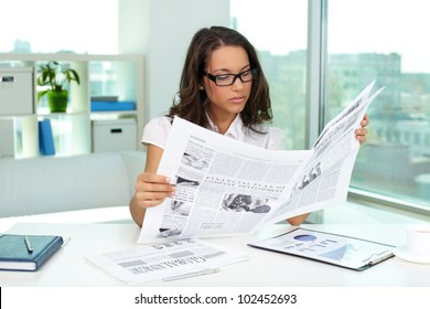 Portrait of a beautiful business lady reading newspaper
