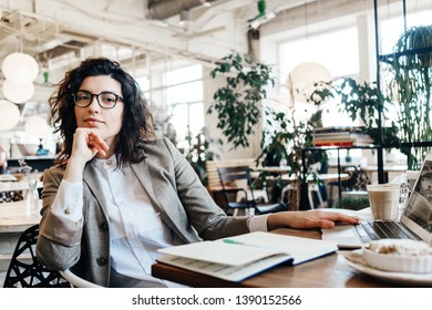 Portrait of beautiful business lady sitting and working at the city eco cafe. Notepad, laptop, coffee, desert on the table