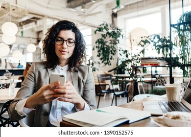 Portrait of beautiful business lady sitting and working at the city eco cafe with mobile phone in hands. Notepad, laptop, coffee, desert on the table