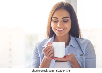 Portrait of beautiful business lady in smart casual wear holding a cup and smiling while sitting at home
