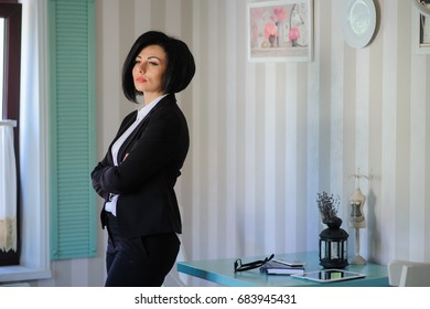 portrait of beautiful  business lady (woman/girl) dressed in black suit in a vintage cafe/office