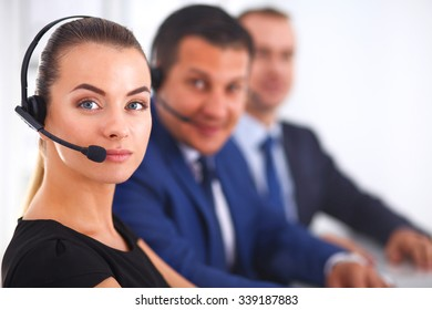 Portrait of beautiful business woman in headphones smiling with colleagues in background