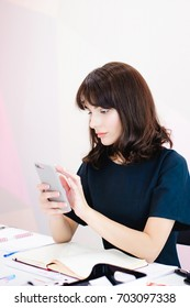 Portrait of a beautiful business woman making notes in a smartphone. Holding a cell phone while sitting in a workplace in a pink office
