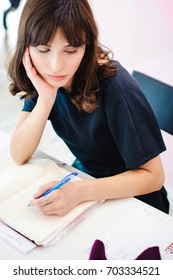 Portrait of a beautiful business woman making notes in a notebook. Holds a pen, sitting in the workplace in a pink office