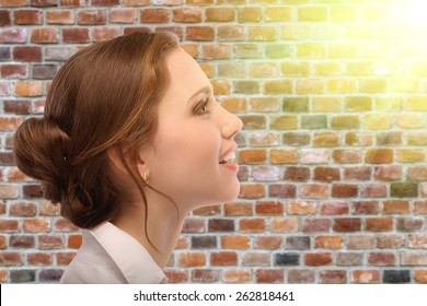 Portrait of beautiful business woman in profile, against background of brick wall