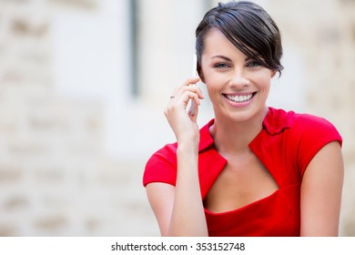 Portrait of beautiful business woman in red dress holding her mobile