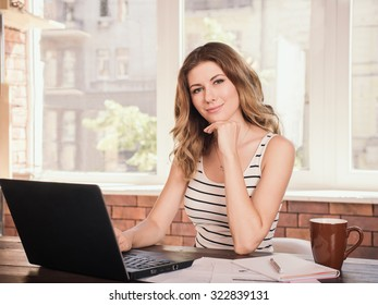 Portrait of a beautiful business woman smiling and sitting near table screen
