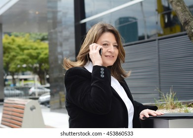 Portrait of beautiful business woman talking on her smartphone. Outdoors.
