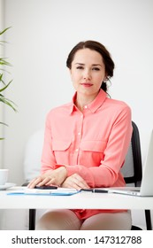 Portrait of a beautiful business woman working on her desk in an office environment