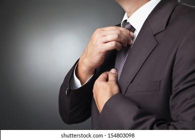 portrait of the beautiful businessman in black costume tie one's necktie