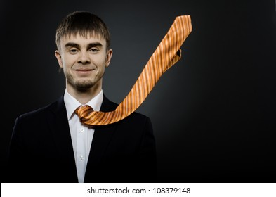 portrait  the  beautiful  businessman careerist in black costume and orange necktie