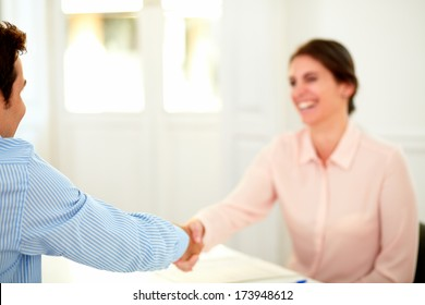 Portrait of beautiful businesswoman giving a hand greeting to handsome businessman while sitting on office desk