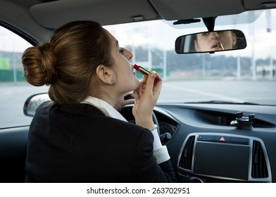 Portrait of beautiful businesswoman looking in mirror at car and applying cosmetics