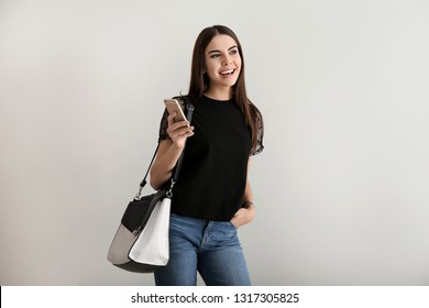 Portrait of beautiful businesswoman with mobile phone on light background