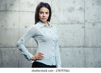Portrait of a beautiful businesswoman over concrete wall and looking at camera