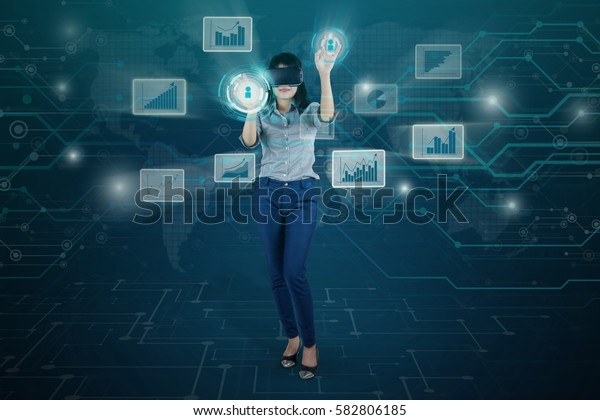 Portrait of beautiful businesswoman using a virtual screen while wearing virtual reality glasses