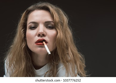 Portrait of beautiful calm blonde girl holding cigarette in mouth, black spots on red lips imitating burned skin. Copy space in right side. Isolated on background