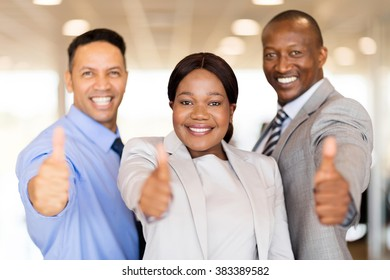 portrait of beautiful car dealership staff giving thumbs up