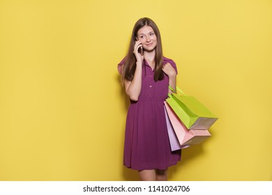 portrait of beautiful casual girl with shopping bag talking on mobilephone at yellow background with copy space