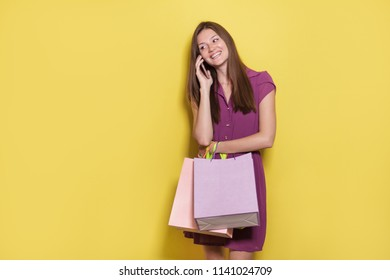portrait of beautiful casual girl with shopping bag talking on mobilephone at yellow background