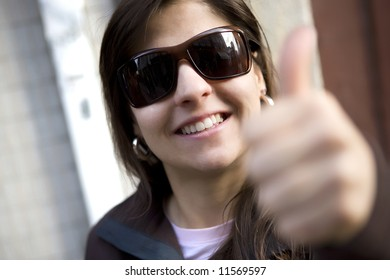 Portrait of beautiful casual woman with thumbs up - selective focus on the sunglasses